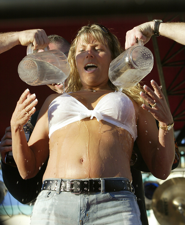 """A volunteer from the audience is doused with ice water during a """"wet t-shirt contest"""" in a bar on Main Street during Bike Week in Daytona Beach,  Florida March 8, 2005. The annual ten-day event attracts motorcyclists of all varieties with over 500,000 expected this year.  REUTERS/Rick Wilking"""