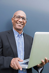 Happy African businessman holding laptop computer