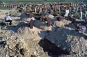Joegoslavie, Bosnie, Bihac , 20-10-1995  Grensgebied tussen kroatie en Bosnie . De Serviers zijn hier een paar weken geleden teruggedreven en de enclave Bihac is ontzet . Vlak buiten de stad Bihac is een nieuwe begraafplaats met oorlogsslachtoffers en gesneuvelde soldaten . Twee vrouwen rouwen bij een vers graf .Oorlogsschade .Foto: ANP/ Hollandse Hoogte/ Flip Franssen