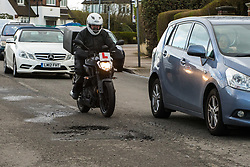 A motorcyclist, to whom potholes represent a considerable danger, negotiates his way along the damages surface of Sidmouth Road in Willesden Green, west London, as the recent cold, wet weather has given rise to the increase in potholes and road surface deterioration in London. London, March 28 2018.