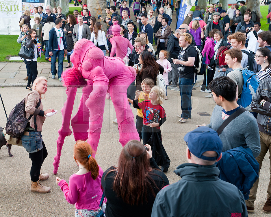 """© Licensed to London News Pictures. 24/06/2012. London, UK.  Aliens land in Greenwich.  """"The Invasion"""" is a Slovenian street theatre act comprising of pink aliens which roam around Greenwich as part of Greenwich Fair.  Greenwich Fair is a part of the Greenwich & Docklands International Festival, taking place between 21-30 June.  Photo credit : Richard Isaac/LNP"""