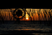 Coconut-leaf decorations silhouetted against setting sun, Jimbaran Bay, Bali, Indonesia. Jimbaran Bay was the location of the second Bali terrorist bombing on October 2, 2005.
