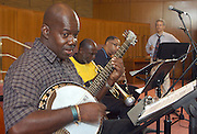 Cantor David Lipp, right, listens as Detroit Brooks, left, jams on a borrowed banjo to El Nora Alila with fellow displaced New Orleans musicians Gregory Stafford on trumpet, Dr. Michael White on clarinet and Mitchell Player on bass (not shown) as they practise Friday, Sept. 23, 2005, in the Shapira Sanctuary at Congregation Adath Jeshurun in Louisville, Ky. for a Saturday show with Cantor Lipp. Congregation Adath Jeshurun brought Dr. Michael White's Quartet together for a series of jazz show to benefit Hurricane Katrina relief titled From Bourbon Street To Bourbon Country. (AP Photo/Brian Bohannon).