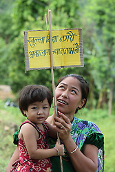 """Meena Shrestha and her unnamed daughter with a sign that says """"Don't defecate in the open. Don't put your life at risk"""" at the community office at WASH User group , Dhangle Tallo Khanitar WASH Project, Udayapur District, Nepal."""