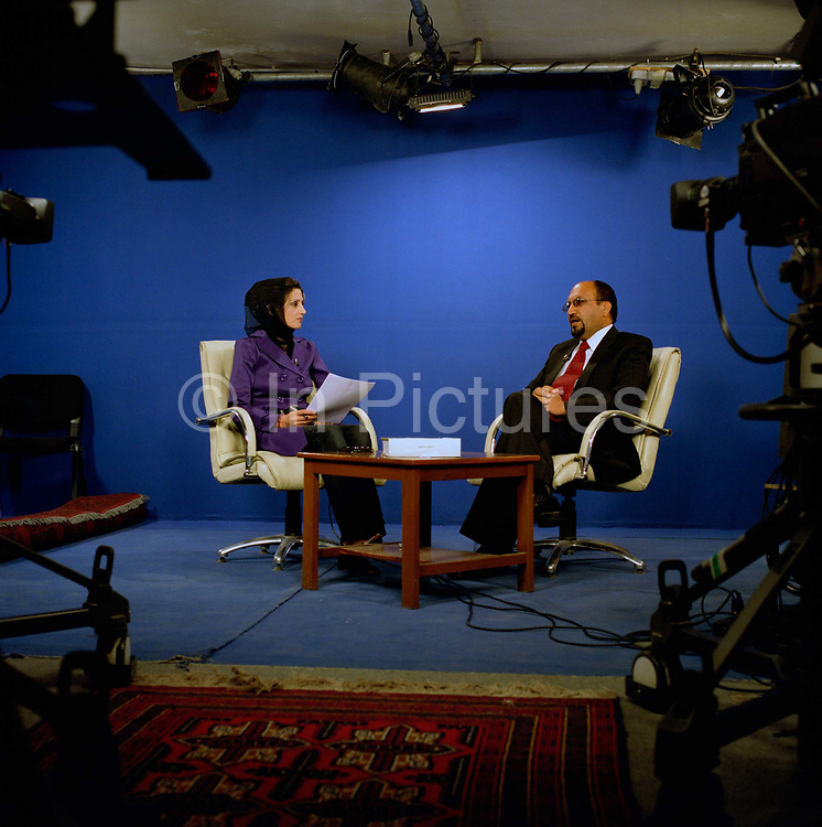 """Mrs Farzana Samimi on her talk show 'Banuî with psychiatrist, Mohammed Yasin Babrak.<br /> <br /> Farzana's show centres on problems faced by Afghan women - largely a taboo subject. Currently, for security reasons guests have to talk by phone: """"I remember one guest - a young girl -  who was forced ( by her parents) to marry."""" Says Farzana. """"But because she came on TV, her parents threatened to kill her"""".  <br /> <br /> One of Farzana's colleagues was shot dead by unknown gunmen in Kabul in May 2005 and Farzana's  husband wants her to stop presenting but she says:  """"The show is very important. For a lot of women, their only source of help is from the TV.""""<br /> A survey of women in Kabul found that 98 percent suffered from post-traumatic stress disorder, chronic depression or severe anxiety. Dr Babrak, Farzana's co presenter says. """"Most women who come to me suffer from mood swings and schizophrenia,"""""""