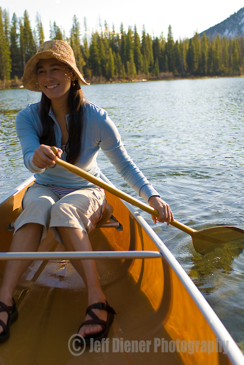 A young woman paddles a canoe on String Lake in Grand Teton National Park, Jackson Hole, Wyoming.