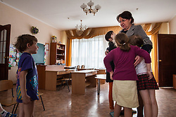 Victoria Mochalova Alexandrovna, the director of Lugansk Orphanage No.1 is hugged by children.