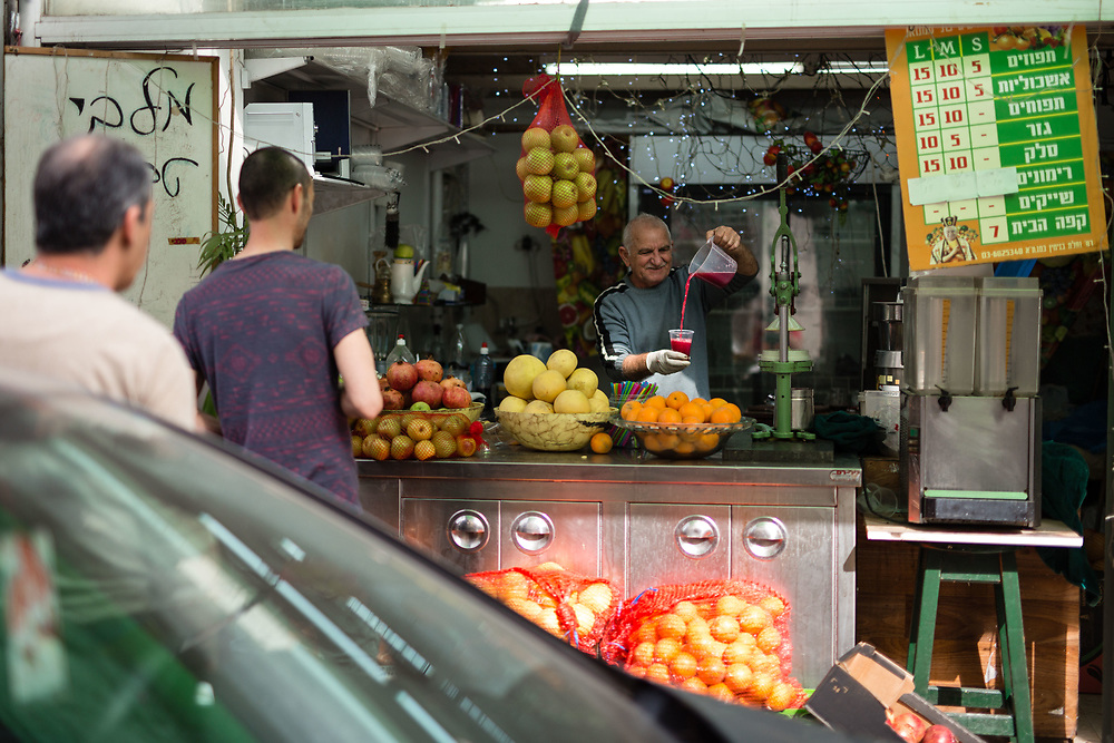 An Israeli vendor pours freshly squeezed juice for customers at his market stall, around the Levinsky Market area in southern Tel Aviv, Israel, on April 16, 2015. The majority of the Levinsky Market vendors are traditional Iranian Jews, many of whom fled the Islamic Republic after Ayatollah Khomeini rose to power in 1979.