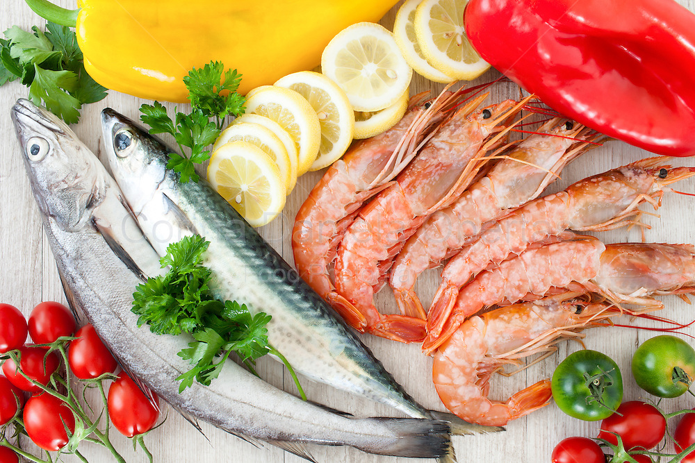 Raw mackerel codfish and prawns with fresh tomatoes peppers parsley and lemon slices flat lay