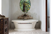 Rustic vintage oval bathtub in a traditional bathroom with garden view