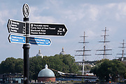 A riverside signpost points along the Thames Path between Tower Bridge, the Thames Barrier and the Cutty Sark cargo clipper whose tall masts are seen near the twin domes of Greenwich Hospital, on 16th September 2021, in London, England.