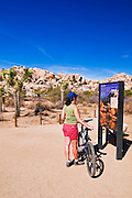 Interpretive sign and visitor at the trailhead to Barker Dam, Joshua Tree National Park, California