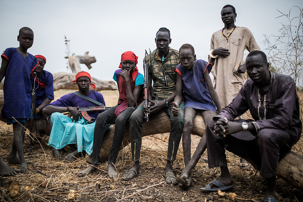 A group of cattle keepers during a cattle vaccination organized by the ICRC. The herds are often guarded 24-7 by armed men. Cows are the most valuable and stable asset families can own and their protection is key. South Sudan, 2020.