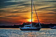 Sailboat with sunset behind it at City Island, New York, part of New York City.