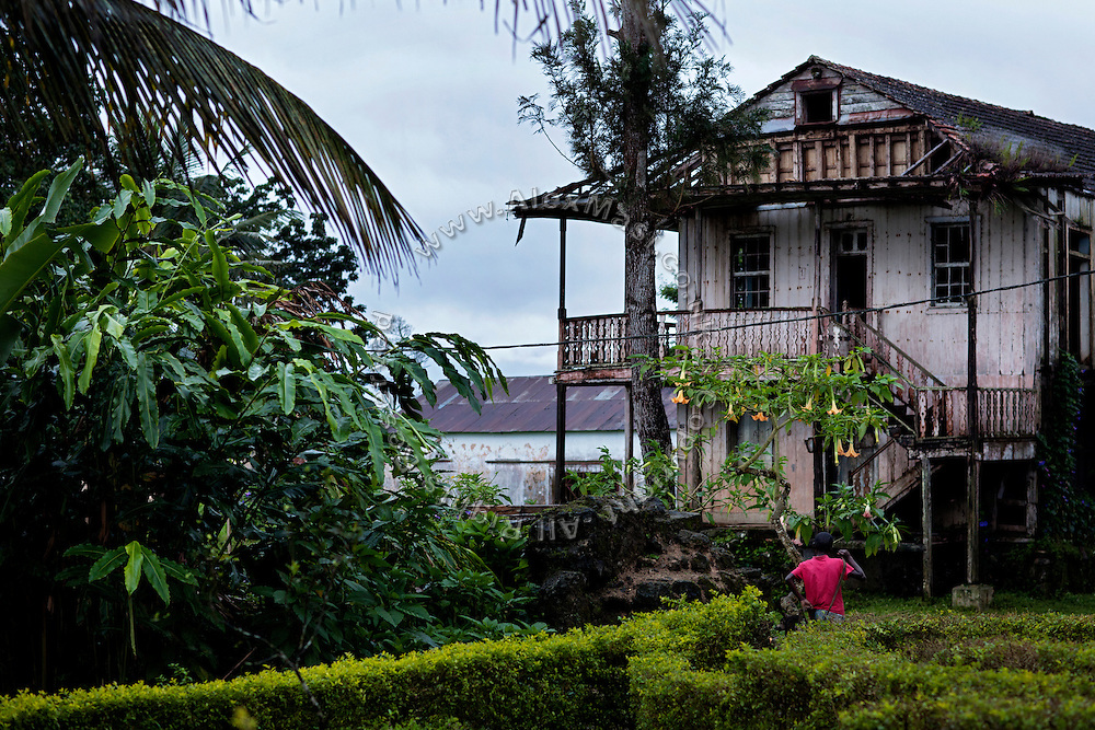 A young man is walking near an old Portuguese house in Claudio Corallo's Nova Moca plantation, on the island of Sao Tome, Sao Tome and Principe, (STP) a former Portuguese colony in the Gulf of Guinea, West Africa.