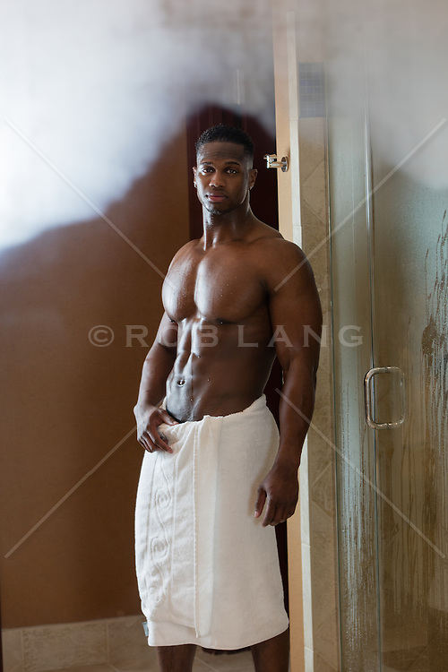 sexy black man in a towel standing in a bathroom