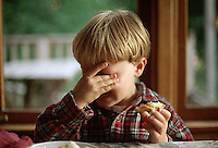 August 1996, San Juan County, Washington, USA --- Four year old Tunui Franken holds his head in one hand and cries with displeasure while eating a biscuit. --- Image by © Owen Franken/CORBIS