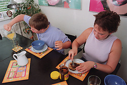 Teenage boy with Downs Syndrome sitting next to sister at kitchen table eating breakfast,