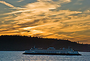 The Spokane, part of the Washington State Ferry system, plies Puget Sound towards sunset over Kingston on the Kitsap Peninsula, Washington.
