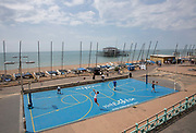Young men play basketball at new basketball court at Brighton seafront on the 19th July 2018 in Brighton in the United Kingdom.