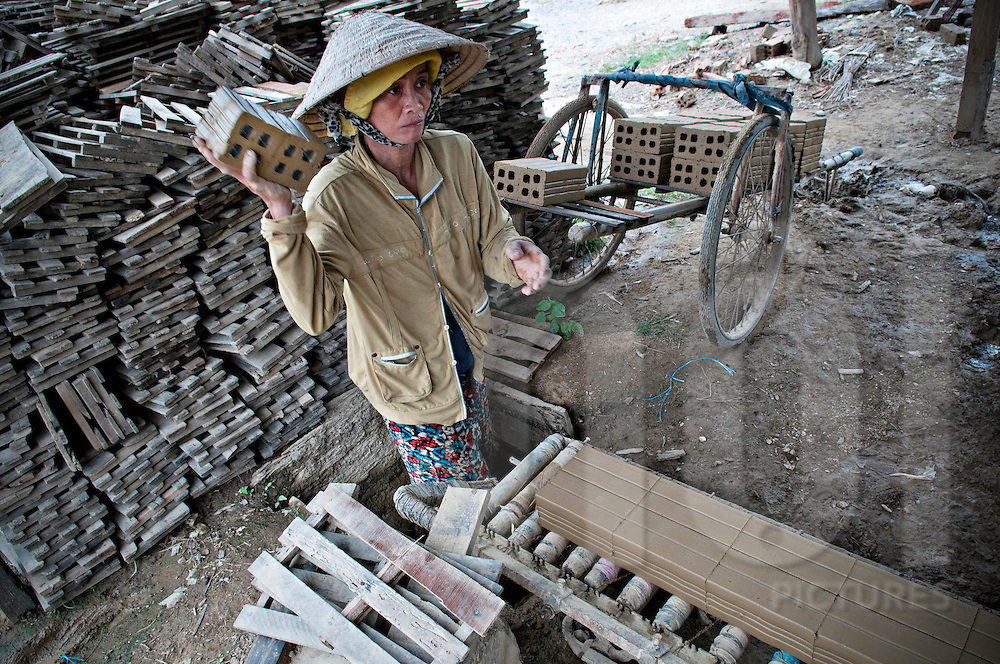 A vietnamese woman is about to throw away a raw brick. Factory in Khanh Hoa, Vietnam, Asia