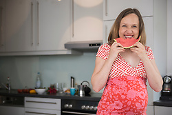 Portrait of a pregnant woman eating watermelon in the kitchen, Munich, Bavaria, Germany