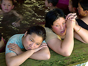 Women relaxing at Gasa tsachhu (hot springs) in Jigme Dorji National Park, Western Bhutan. At Gasa hot springs there are five pools with water temperature ranging from mild to extremely hot. During the winter months when farming work is done, families from all over Bhutan come here to relax in the restorative pools for many days.