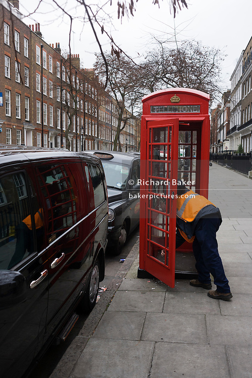 An employee clears broken glass from the lower pane of a public phone box in a central London street.