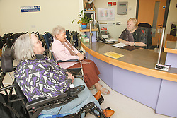Receptionist with wheelchair users at reception for a resource for people with physical and sensory impairment.