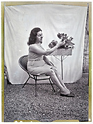 portrait of woman sitting in outdoor classic vintage studio style with flower plant 1950s France