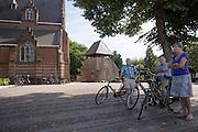 Ouderen staan op het plein voor de kerk in Bergeijk onder een boom met hun fiets.<br /> <br /> Elderly people stand on the square before the church in Bergeijk under a tree with their bike.