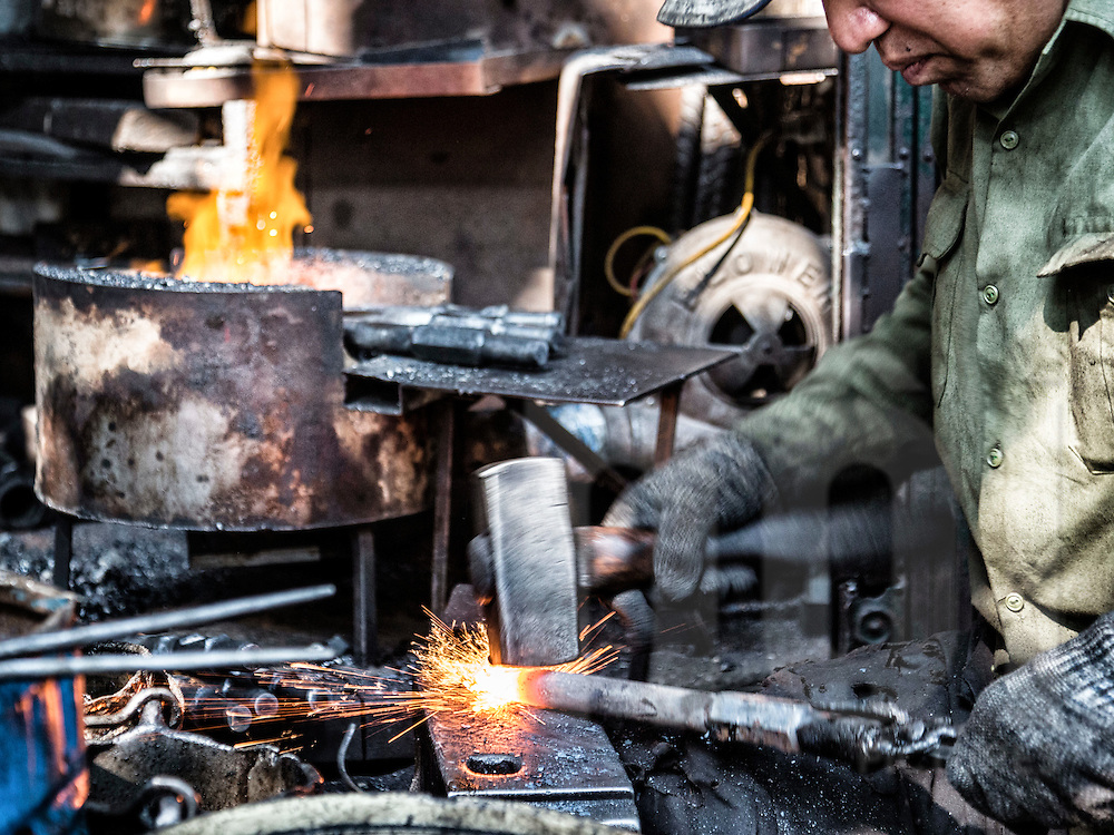 A blacksmith forges and hammers metal products along Lo Ren street in Hanoi's Old Quarter, Vietnam
