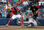 ATLANTA, GA - JUNE 14:  Third baseman  Joaquin Arias #13 of the San Francisco Giants slides into home plate before a throw to catcher Brian McCann #16 of the Atlanta Braves while home plate umpire Gary Darling #37 looks on at Turner Field on June 14, 2013 in Atlanta, Georgia.  (Photo by Mike Zarrilli/Getty Images)