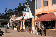 Mature elderly tourist couple window shopping in local shops in the quaint coastal village of Cambria, California