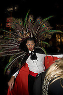 Man costumed as a vampire with peacock feathers