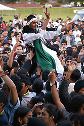 Man being lifted above crowd of people at the Nottingham Mela,