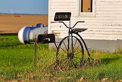 an old high wheel bicycle repurposed as a rural mailbox stand sits in front of an old building heated by LP Gas Some images in this series have been digitally altered.  <br />
