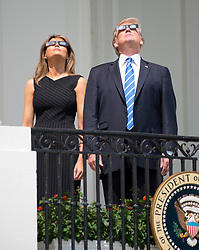 United States President Donald J. Trump, right, and first lady Melania Trump look at the partial eclipse of the sun from the Blue Room Balcony of the White House in Washington, DC, USA, on Monday, August 21, 2017. Photo by Ron Sachs/CNP/ABACAPRESS.COM