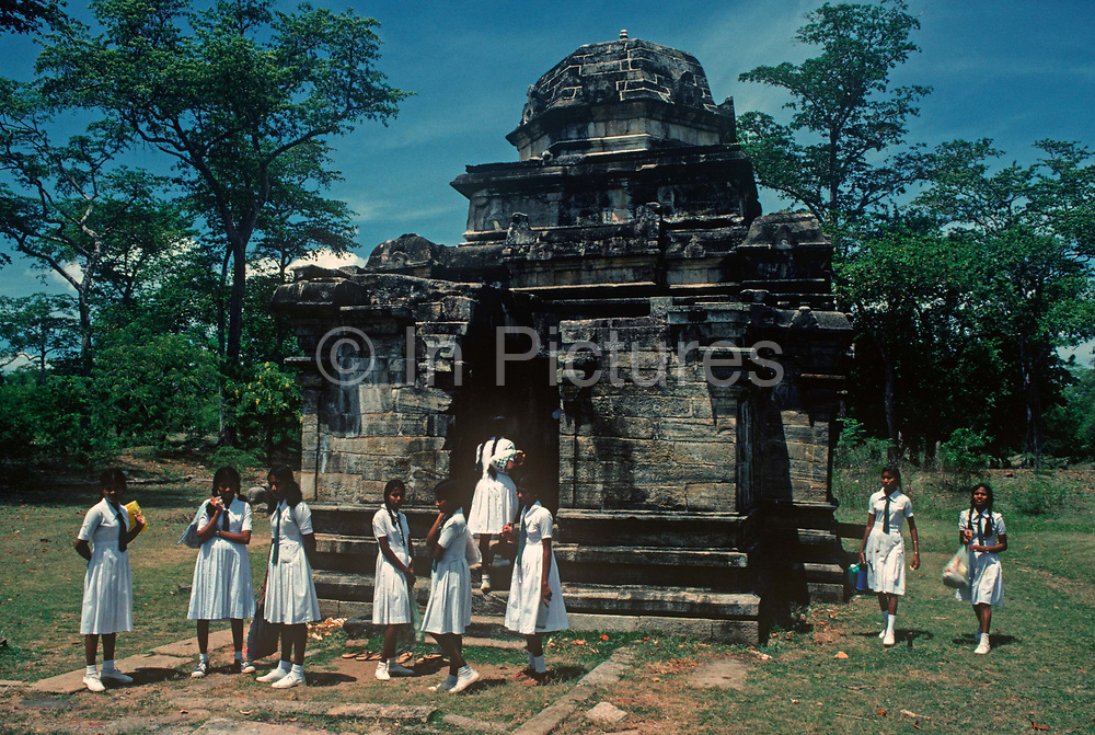 1980s Sri Lankan schoolgirls in clean white uniforms and visiting the ancient city of Polonnaruwa, stand alongside the Shiva Devale temple, on 12th Arpil 1980, at Polonnaruwa, Sri Lanka. Shiva Devale No 2 is the oldest structure in Polonnaruwa and dates from the brief Chola period, when the Indian invaders established the city. Built in the 11th century, this Hindu temple built entirely of stone. Within in the sanctum is a stone carved lingam or phallus, a symbol of Hindu god Diva. In front of the temple is the Nandi bull, God Shiva's vehicle. Polonnaruwa, Sri Lanka's splendid medieval capital was established as the first city of the land in the 11th Century, A.D.