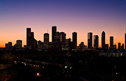 Silhouette of downtown Houston, Texas skyline with a colorful sunset sky.