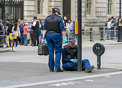 Whitehall, London, May 24th 2017.  Wreaths are laid at the Cenotaph on Whitehall in London as The Band of the Welsh Guards and the Colour Guard of the United Nations Veterans Association lead members of the diplomatic corps and wreath layers from The Royal United Services Institute as they observe The International day of United Nations Peacekeepers, amid tight security. PICTURED: Police examine street furniture including manholes and traffic lights ahead of the ceremony as Whitehall is cordoned off.