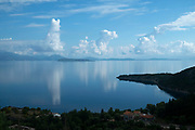 View out with incredible cloud formations across the Ionian Sea towards the nearby islands and mainland at Rachi, near Kioni in Ithaca Greece. Ithaca, Ithaki or Ithaka is a Greek island located in the Ionian Sea to the west of continental Greece. Ithacas main island has an area of 96 square kilometres. It is the second-smallest of seven main Ionian Islands.