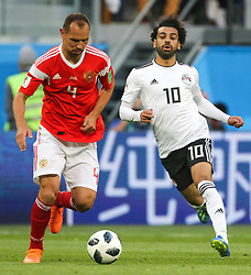 June 19, 2018 - Saint Petersburg, Russia - Sergey Ignashevich (L) of the Russia national football team and Mohamed Salah of the Egypt national football team vie for the ball during the 2018 FIFA World Cup match, first stage - Group A between Russia and Egypt at Saint Petersburg Stadium on June 19, 2018 in St. Petersburg, Russia. (Credit Image: © Igor Russak/NurPhoto via ZUMA Press)