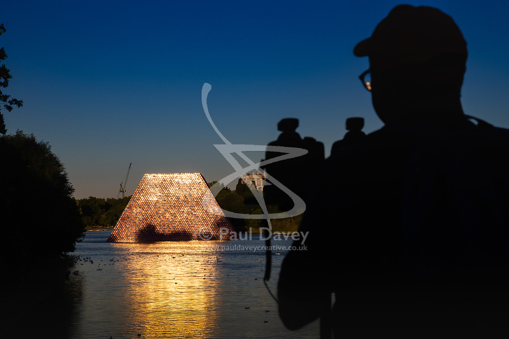 A Photographer shoots 3-D images as the setting sun is reflected onto the water, of artist Christo's 'Mastaba', an installation made up of over 7,000 barrels floating on The Serpentine in London's Hyde Pak. London, July 02 2018.