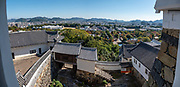 """Rooftop view of Himeji Castle, built 1609, Hyogo Prefecture, Japan. Himeji Castle is both a national treasure and a UNESCO World Heritage Site. Unlike many other Japanese castles, it was never destroyed by war, earthquake or fire and survives to this day as one of the country's twelve original castles. History: Starting as forts built in 1333 and 1346, Himeji Castle (aka White Heron Castle or White Egret Castle) was remodeled in 1561, remodeled in 1581, enlarged in 1609 to its present complex, extensively repaired in 1956, and renovated in 2009-15. Displayed inside are historic samurai armour and swords. From the upper floors, view fish-shaped roof ornaments that are believed to protect from fire. Across the moat, visit Koko-en, a pleasing reconstruction of former samurai quarters, nine Edo period homes, plus movie-set gardens. Himeji Castle starred in the 1967 James Bond movie """"You Only Live Twice""""; in Akira Kurosawa's 1980 film """"Kagemusha"""" and 1985 """"Ran""""; and in the 1980 television miniseries Shogun (portraying feudal Osaka castle). By train, Himeji is 3 hours round trip from Kyoto. This image was stitched from multiple overlapping photos."""