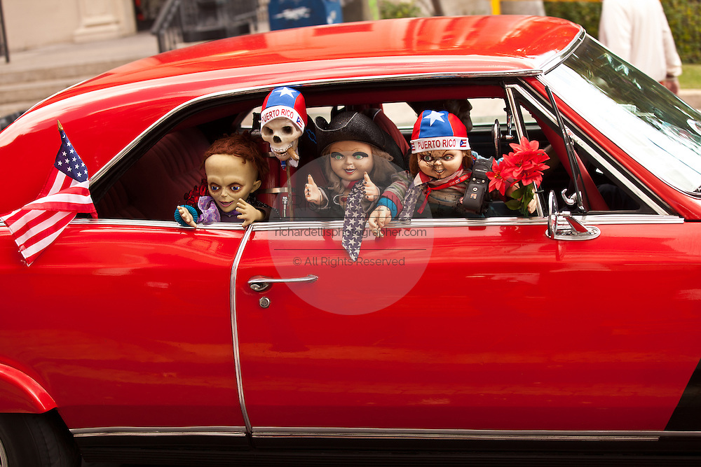 A vintage muscle car decorated with dolls and flags in Old San Juan, Puerto Rico.