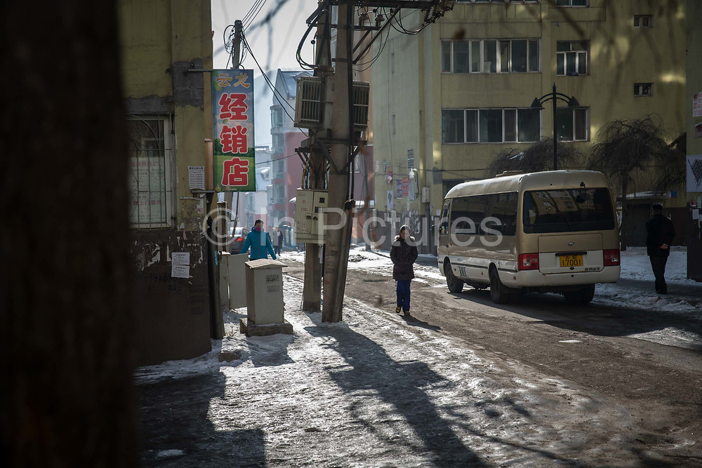 Residents walk past an intersection in the Erdaojiang district in Tonghua, Jilin province, China, on Wednesday, Jan. 6, 2016. The citys once-vaunted state-run steel mills have slipped inexorably into decline, weighed down by slumping global markets, a changing economy, and the burden of costs and responsibilities to the people of the town they fostered. Previous attempts to privatise the enterprise have met with stiff resistance, one such attempt resulted the mob lynching and death of a private businessman who wanted to invest and streamline the operation.