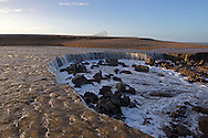 Major breach in shingle defence sea wall at Salthouse following major flood surges of December 2013, resembling a mini Niagra, Norfolk UK