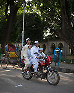 Four people, two Muslim men and two Muslim boys, ride on a motorbike on a street in Dhaka, Bangladesh (2017)