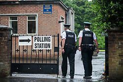 PSNI officers walk into the South Belfast Polling Station at St. Nicolas Parish Hall, Belfast, as voting gets underway in the 2017 General Election.
